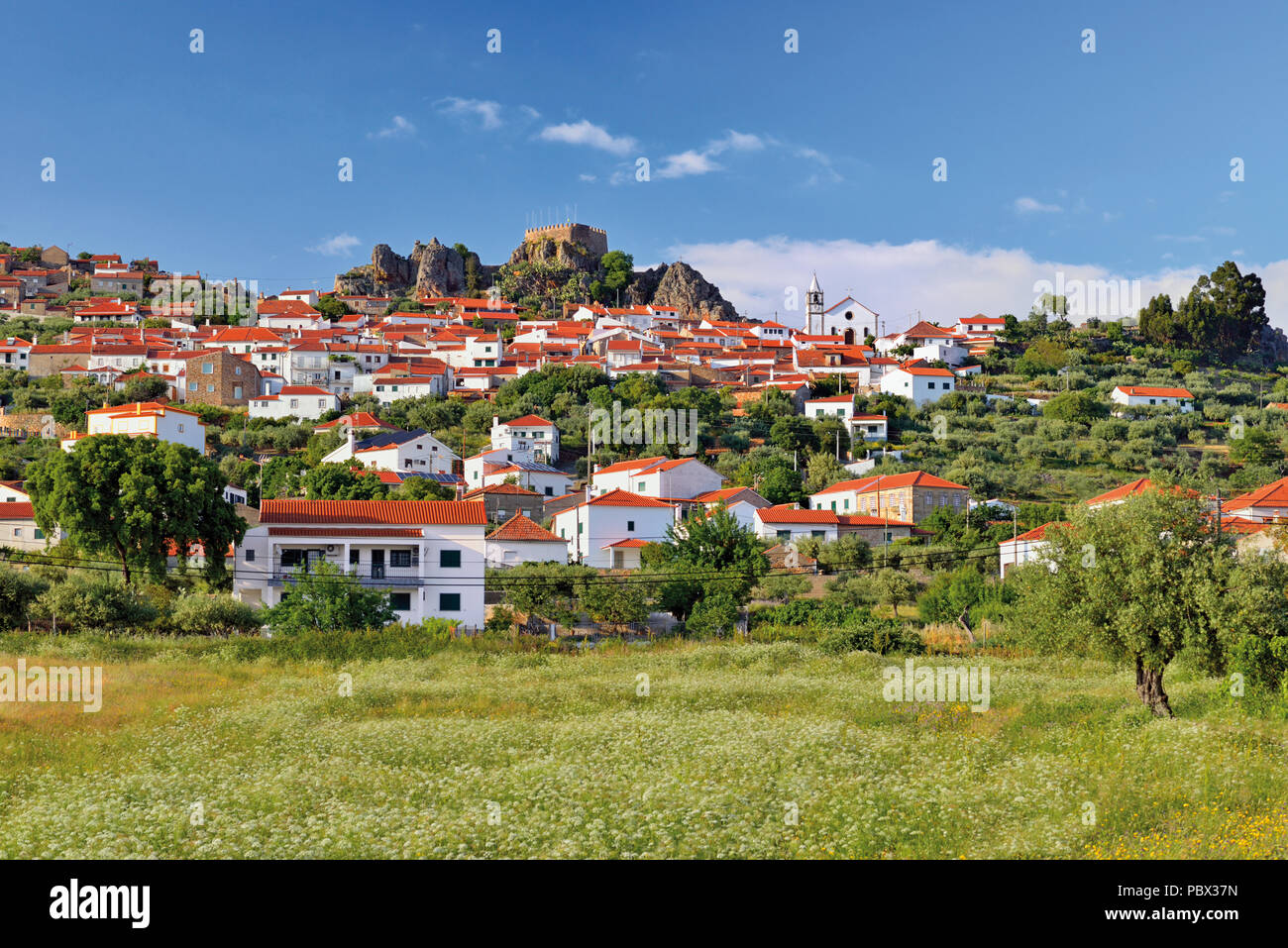 View to a charming small village with a castle ruin on the top - Stock Image