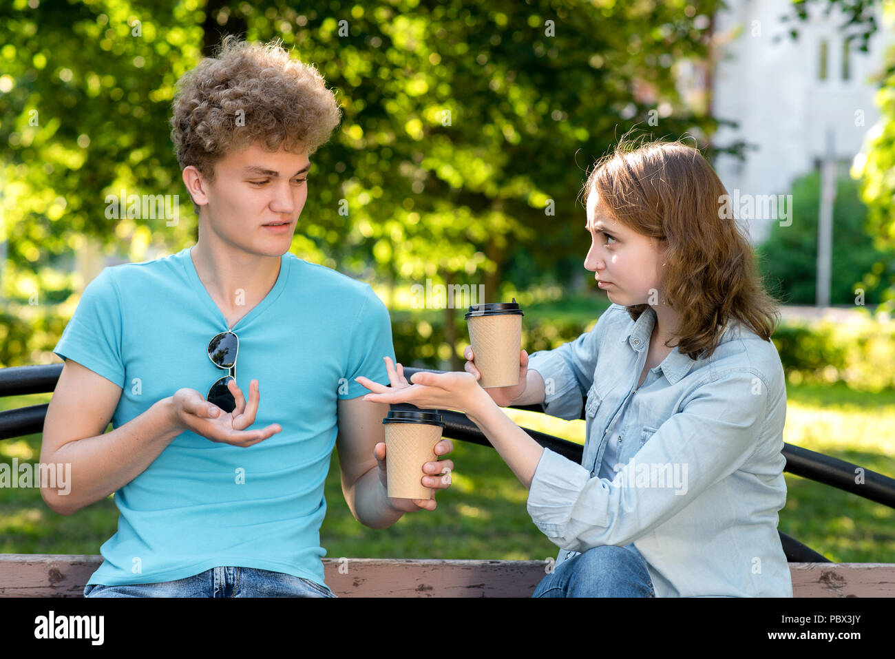 A boy and a girl communicate in nature. In summer after the lessons on the bench. The concept of misunderstanding. Claims each other. Emotionally gestures with hands. Resentment and disagreement - Stock Image