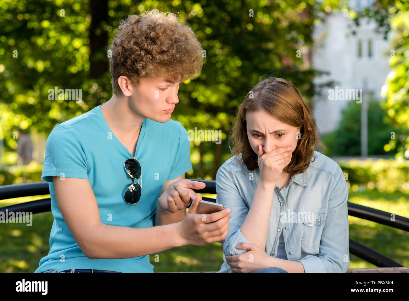 A boy with a girl in summer outdoors. A guy is holding hands with a smartphone pointing his finger at the phone. Emotions of mistrust. The problem is in relationship. Corrections in correspondence. - Stock Image