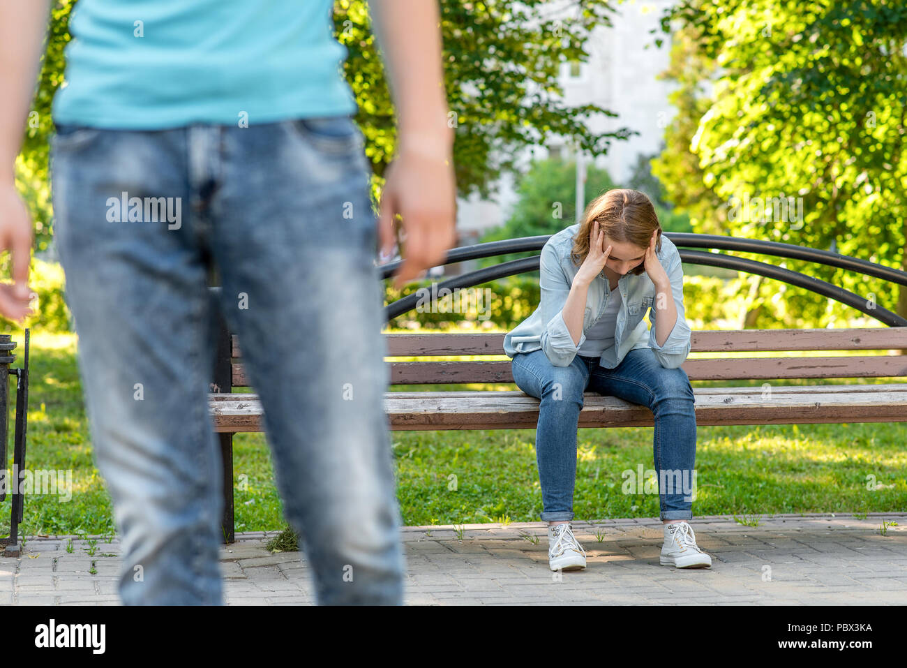 The girl is crying on bench. In the summer in the park in nature. The young man leaves her. Frustration is a mistrust. Problems in the family break the relationship. - Stock Image