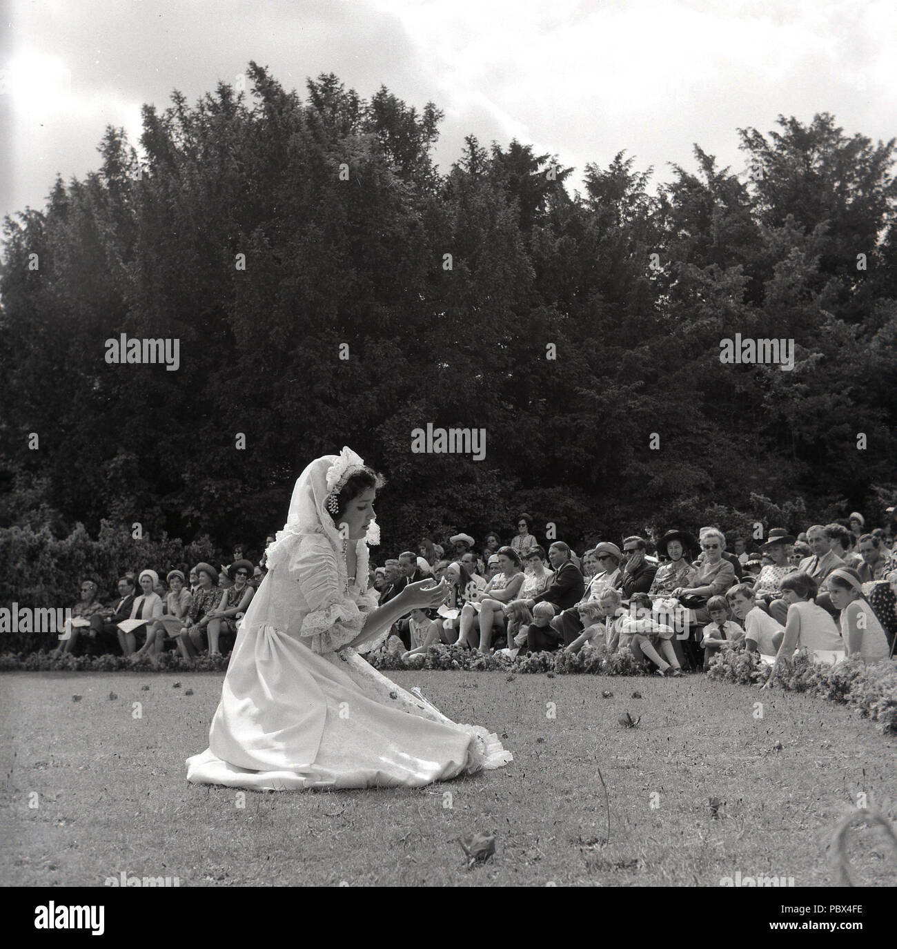 1964, Tring arts, a young girl performing in the open-air outside infront of a seated audience in the grounds of the Tring Park School for the Performing Arts, orginally the Arts Educational School. - Stock Image