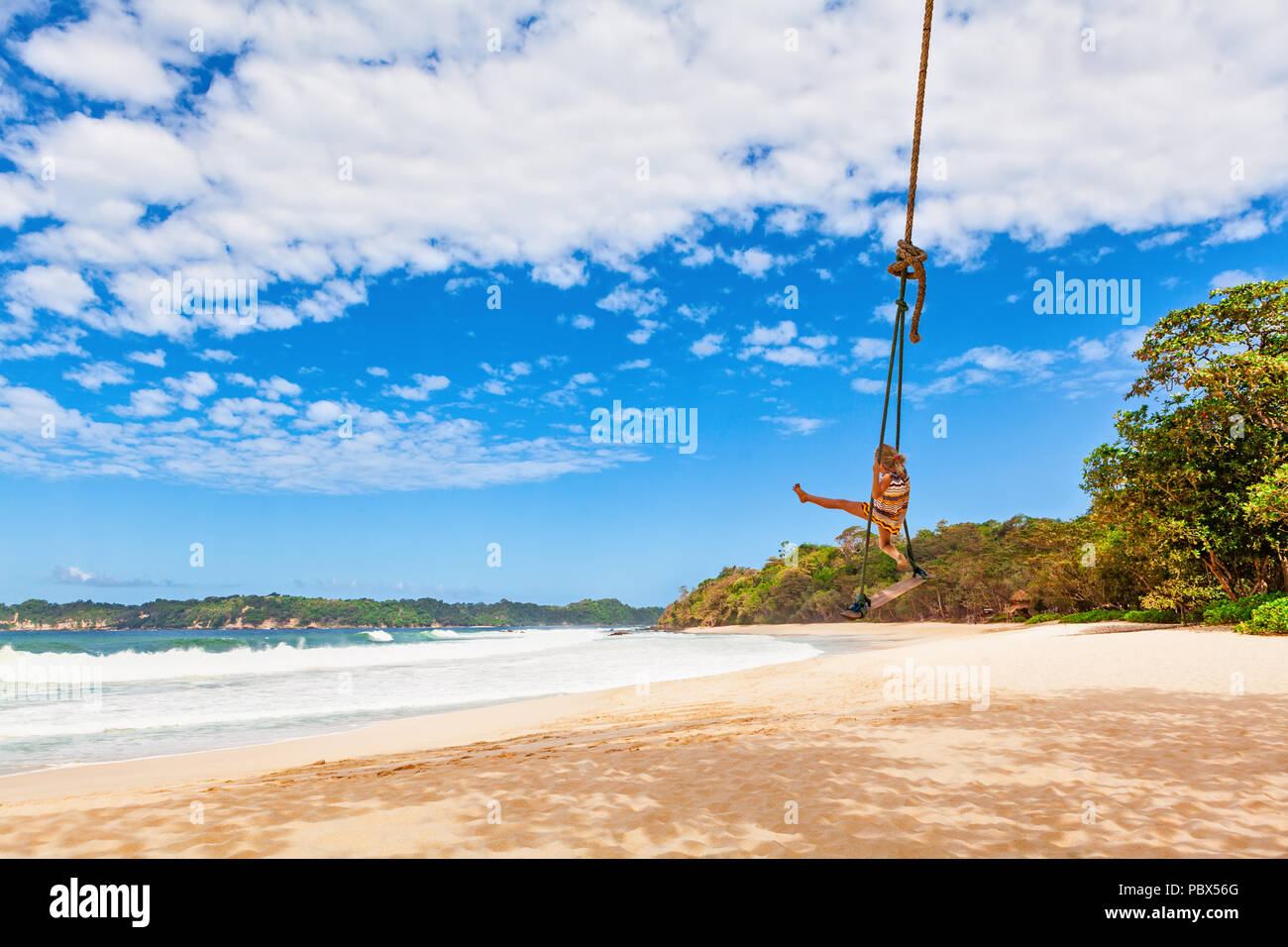Happy girl have fun swinging high in mid air. Flying up on rope swing on sea beach. Travel adventure on paradise tropical island. Family holidays - Stock Image