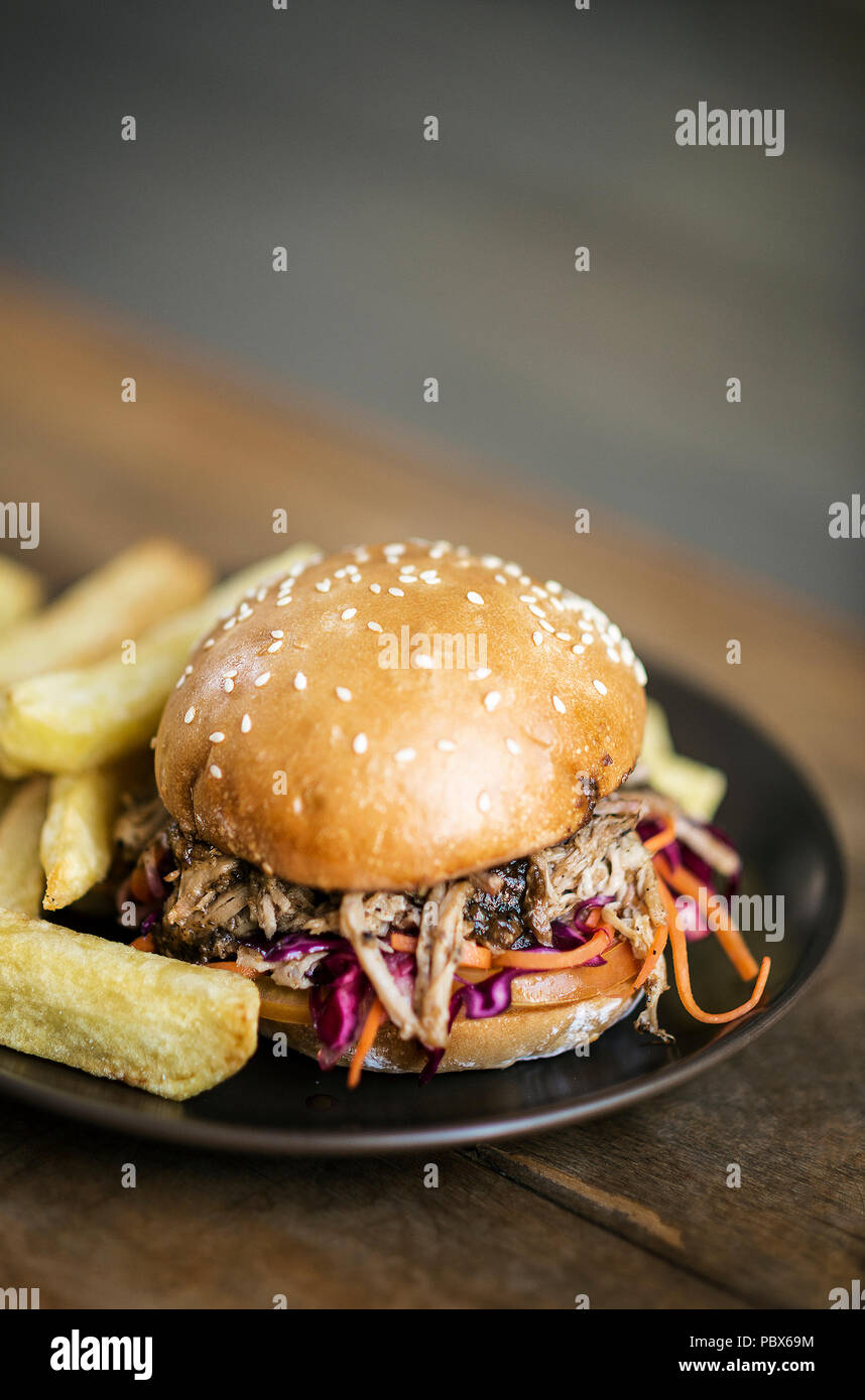 pulled pork and coleslaw salad burger sandwich with french fries snack meal - Stock Image