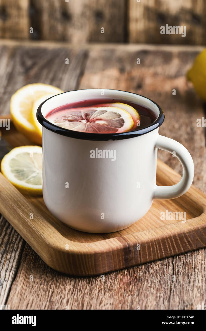 Hot fruit tea with lemon slices in white rustic mug on wooden table, cozy hot winter drink - Stock Image