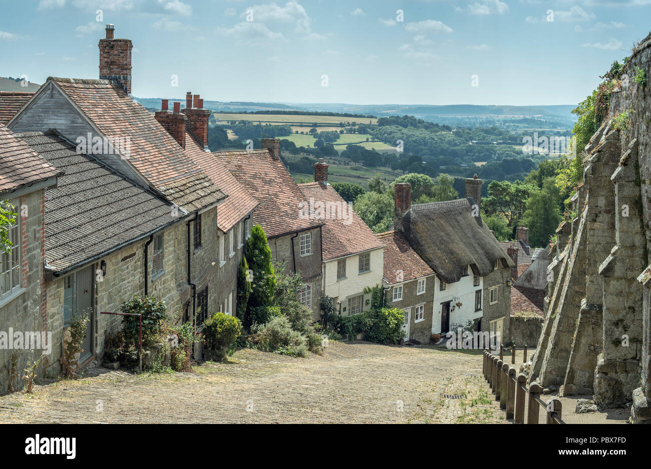 Traditional British English town landscape view with thatched cottages, old houses and farmland - Stock Image