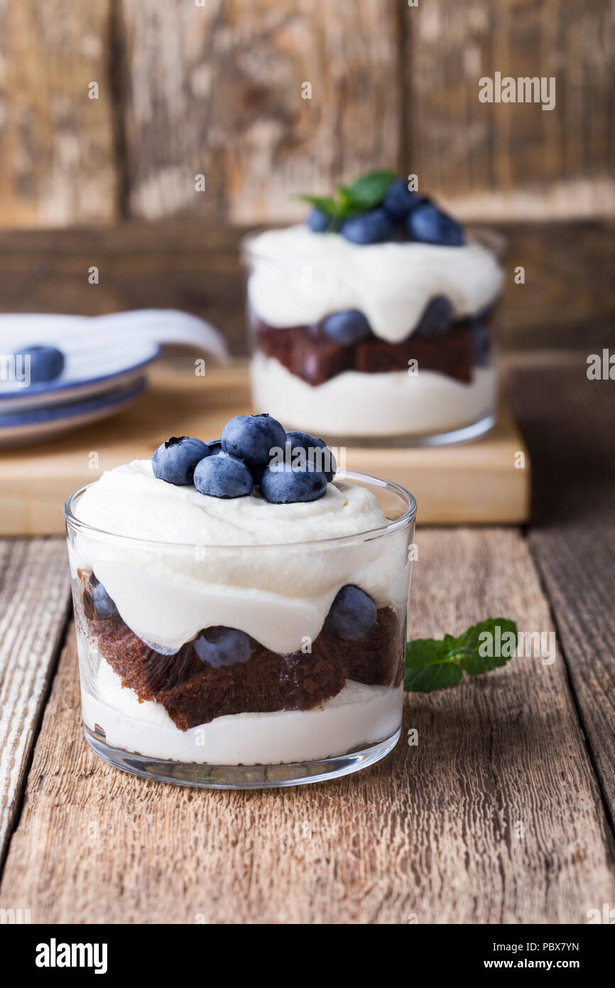 Blueberry chocolate cake  trifle in glass on rustic wooden table, delicious summer dessert - Stock Image