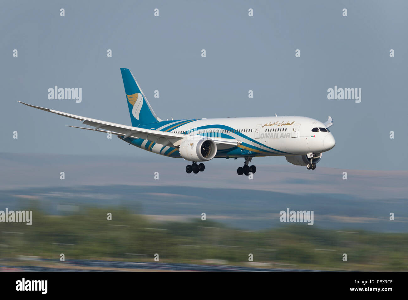 An Oman Air Boeing 787-8 comes in to land at Manchester Airport, UK. - Stock Image