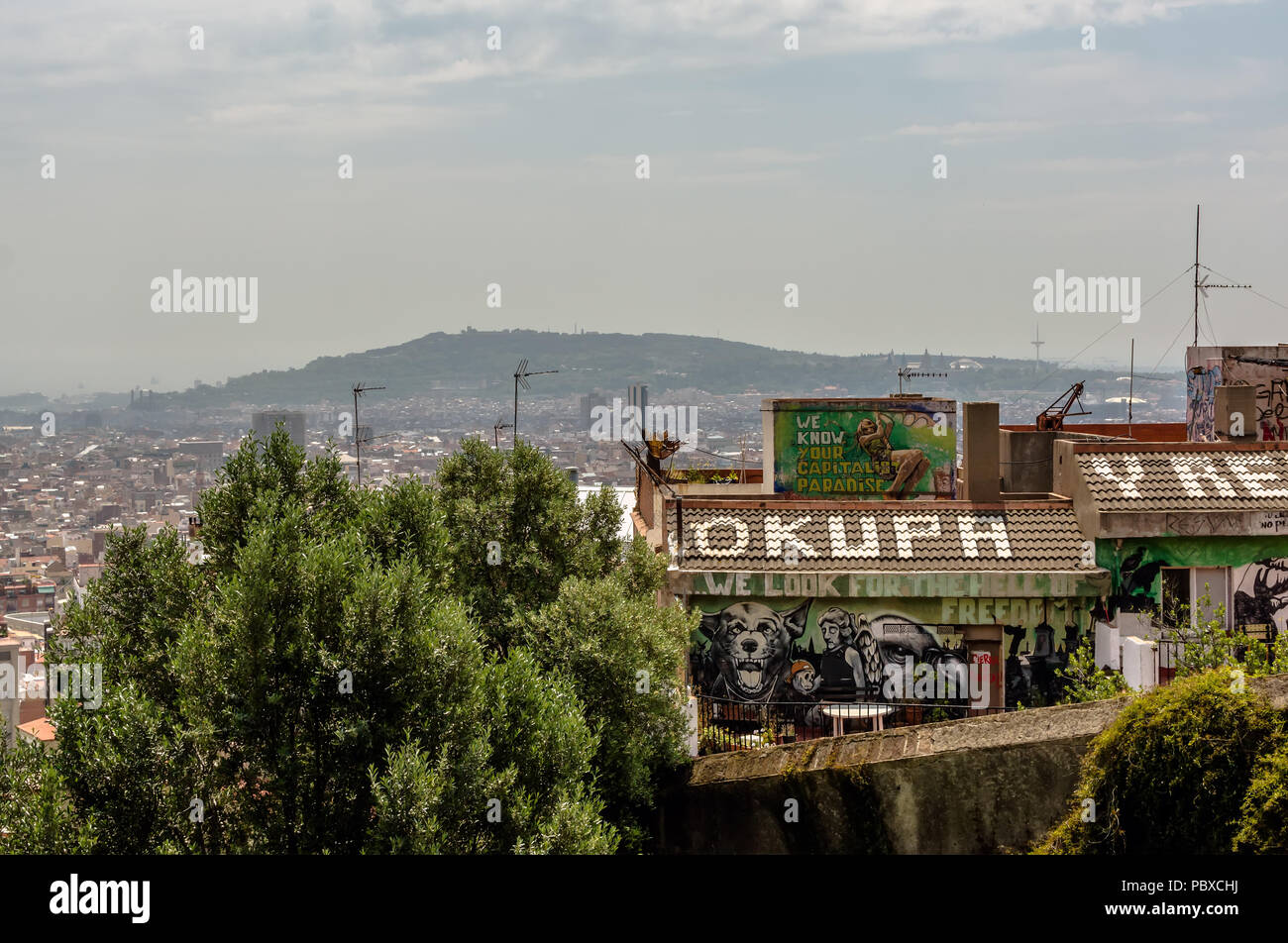 View to the squatted social center roof from Park Guell. Roof sign 'Okupa y Resiste' means' 'Squat & Resist'. - Stock Image