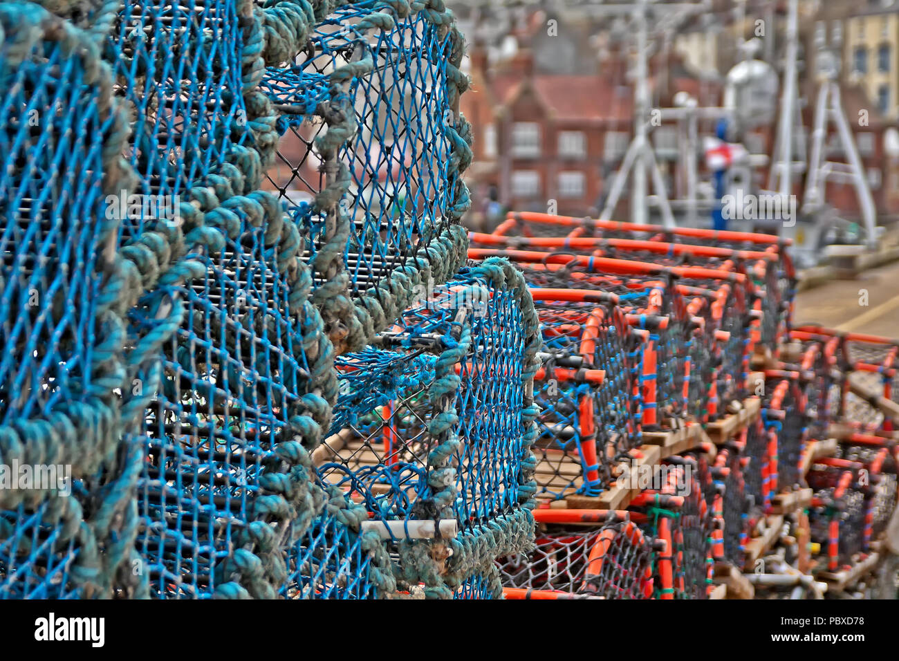 Lobster and crab pots piled high along the dock side of Scarborough's harbour. Stock Photo