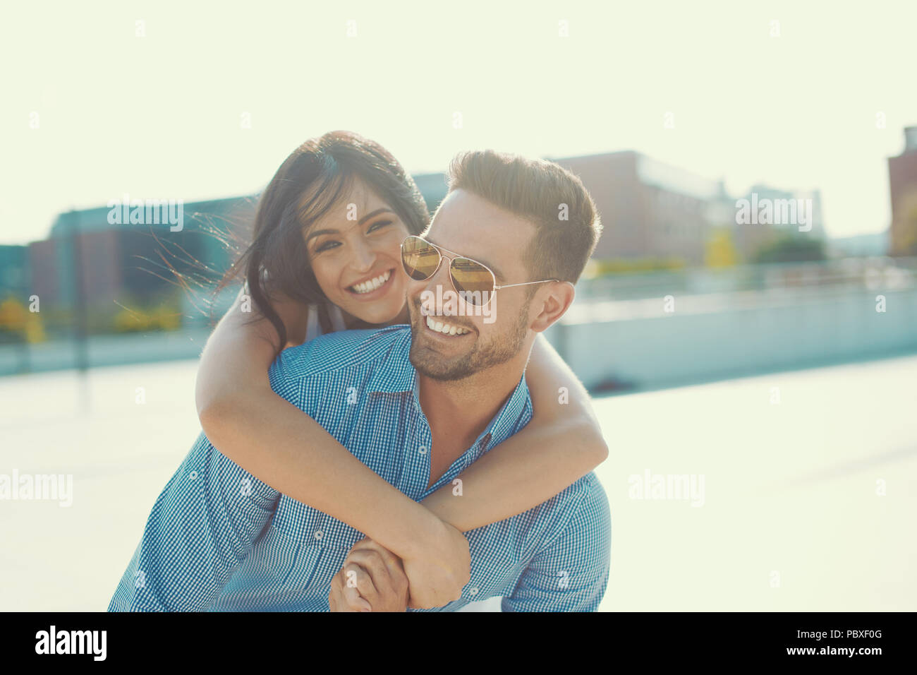 Happy young woman embracing stylish man from back outdoors in sunset, piggyback ride - Stock Image