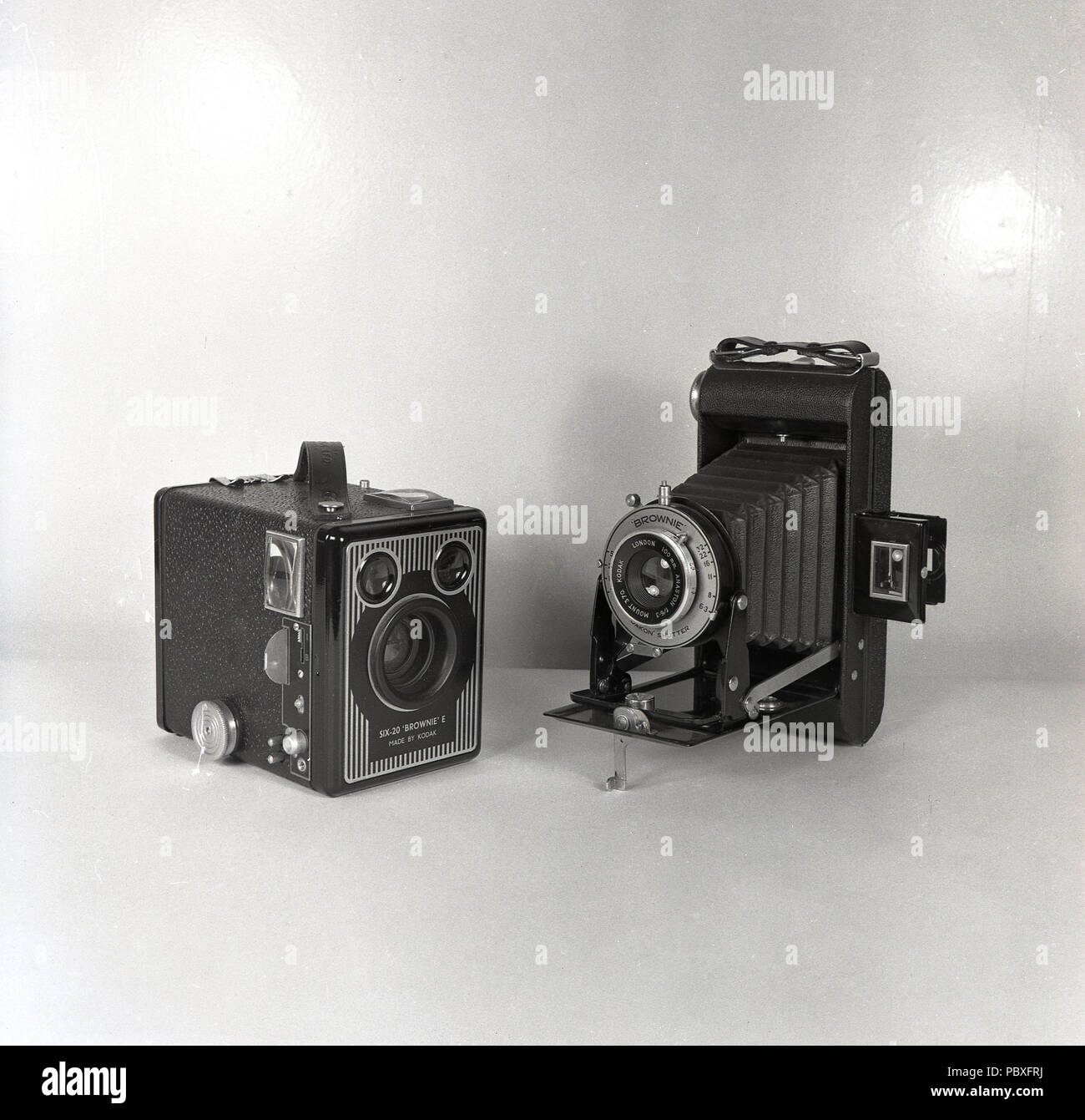 1950s, historical, picture shows two of the most popular amateur film cameras of the era, a Kodak 'Brownie' box camera and a folding medium format camera. - Stock Image
