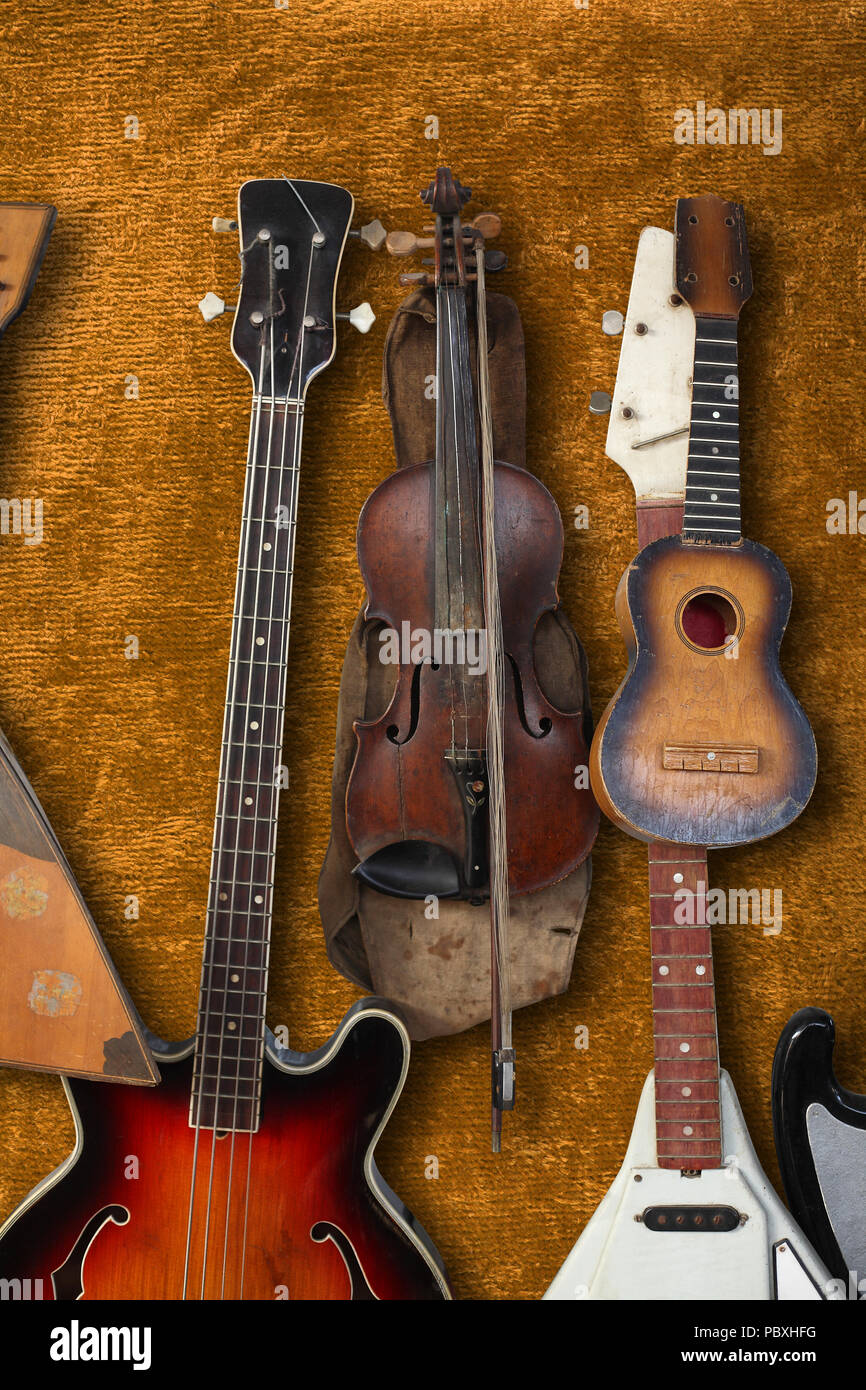 Musical instrument - Vintage bass guitar, acoustic, violin, balalaika on a brown plush background. - Stock Image