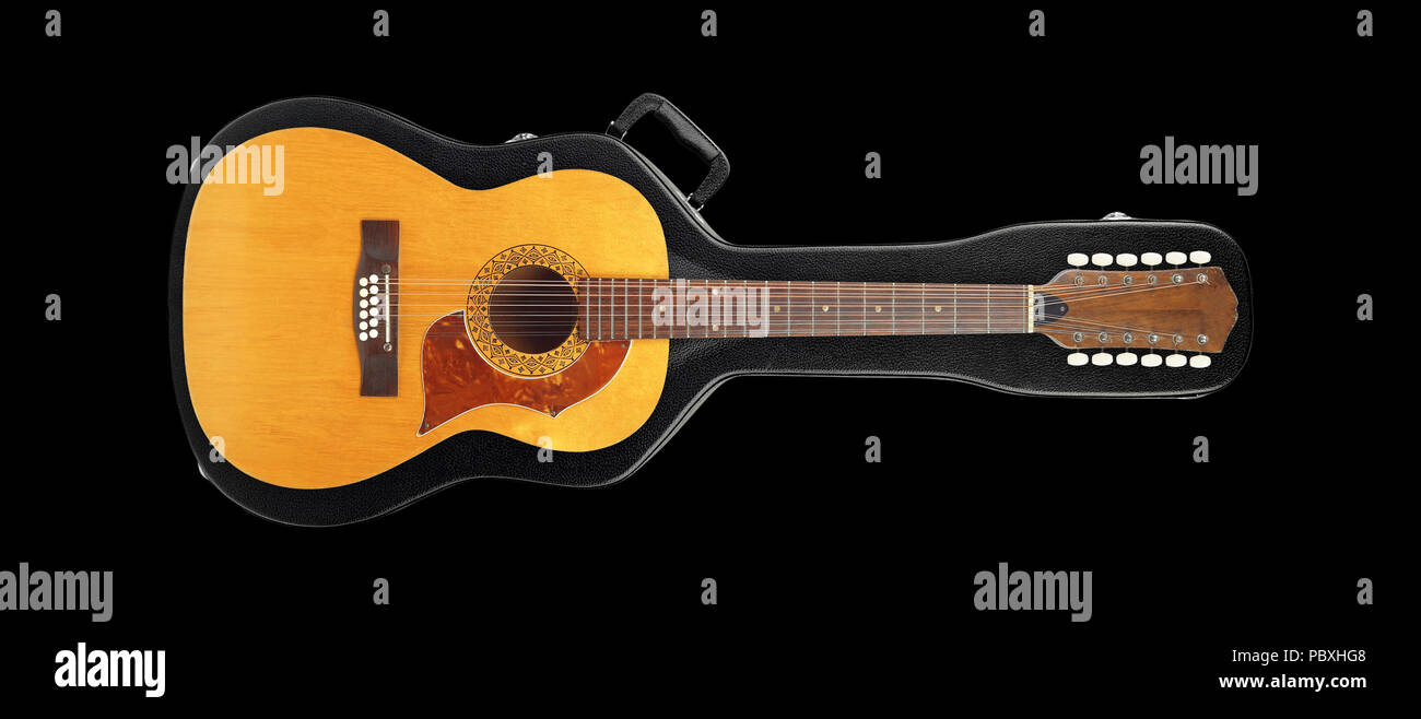 Musical instrument - Vintage twelve-string acoustic guitar from above on a hard case hard case isolated on a black background. Stock Photo