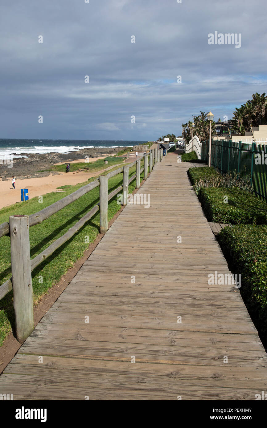 Coastal boardwalk above the sandy beach at Ballito a holiday town located in KwaZulu-Natal, South Africa - Stock Image