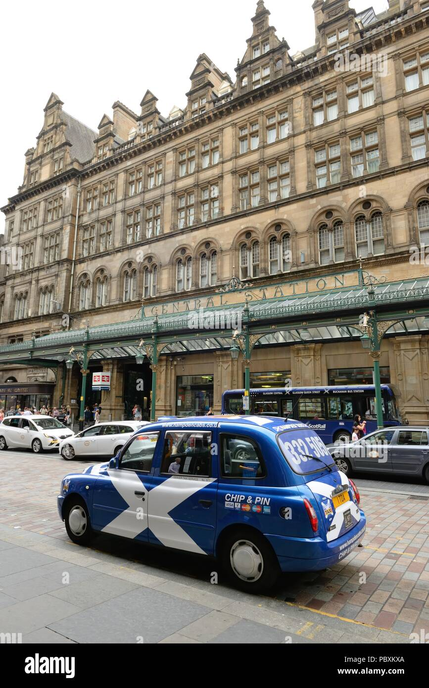 The blue and white Saltire flag adorns a taxi at the main entrance of Glasgow Central train station in Scotland, UK and the Central hotel above. - Stock Image