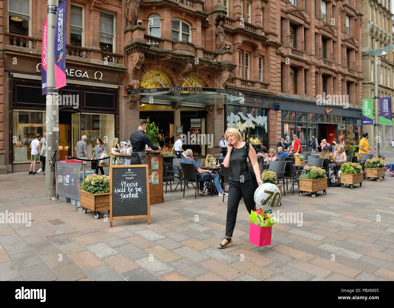 A woman on mobile phone shopping for birthday presents outside Argyll Chambers on Buchanan St. pedestrian precinct, Glasgow city centre, Scotland, UK - Stock Image