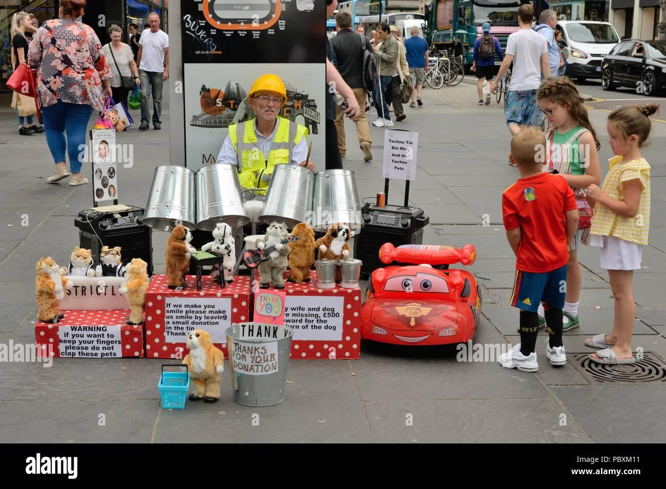Children being entertained by the Techno Tin Bin Man busking on Argyle Street, Glasgow city centre, Scotland, UK - Stock Image