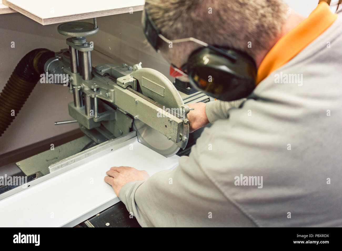 Tinner cutting metal sheets in his workshop with saw - Stock Image