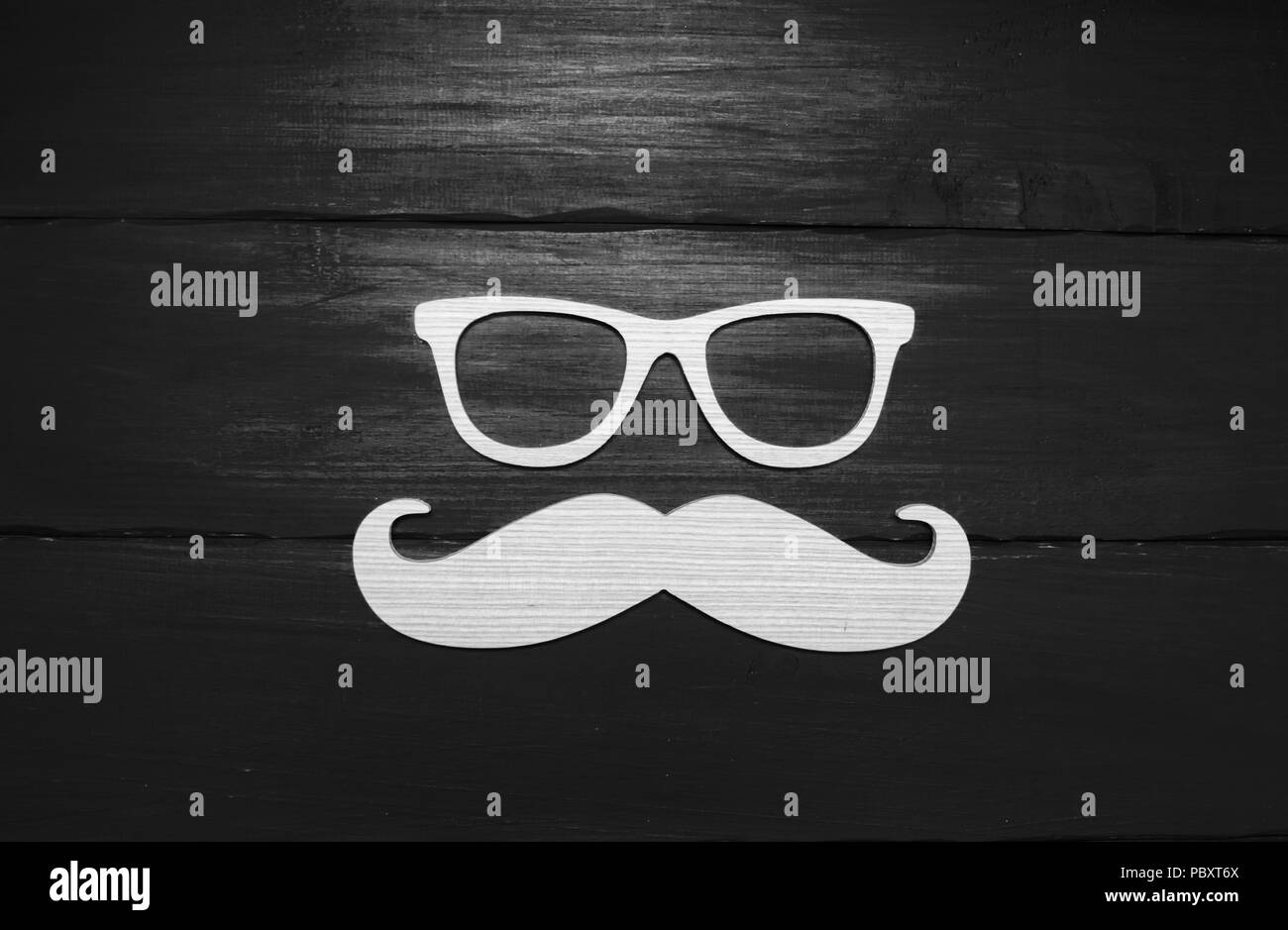 Hipster  concept. Wooden mustache and wooden glasses on a blue background - Stock Image