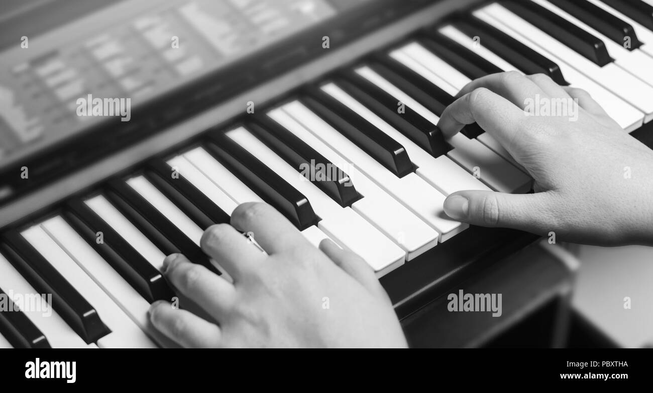 Close-up of a music performer's hand playing the piano, man's hand, classical music, keyboard, synthesizer, pianist - Stock Image