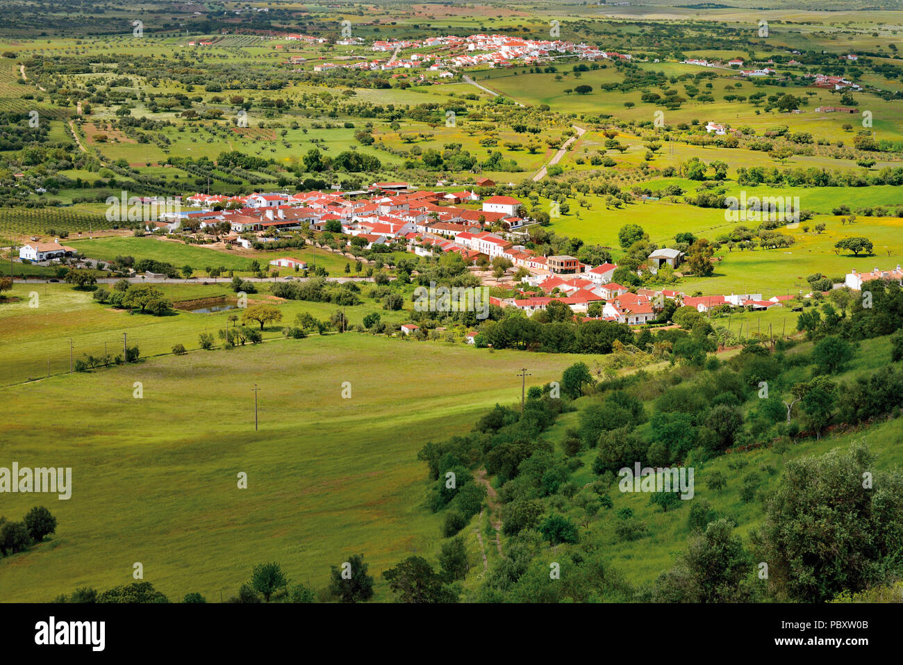 View to two villages in the middle of a wide flat and green landscape - Stock Image