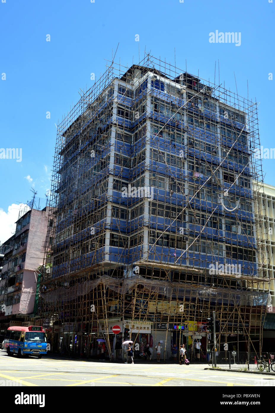 Building covered by bamboo scaffolding - Stock Image