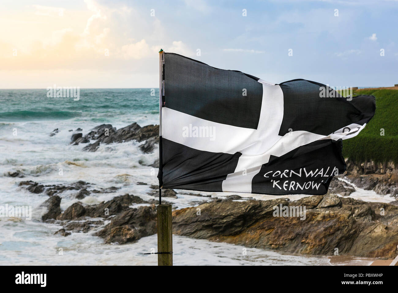 A St Piran flag fluttering in the wind on the coast at Fistral in Newquay Cornwall. - Stock Image