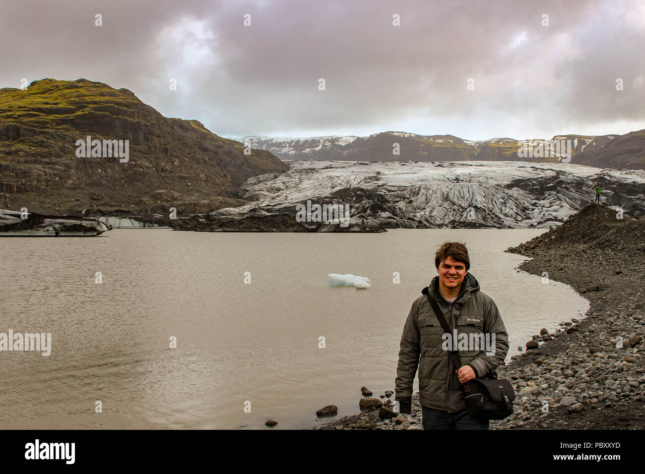 tourist stands by a glacier in Iceland on a rainy and depressing day, this kind of weather defines Iceland in the winter. - Stock Image