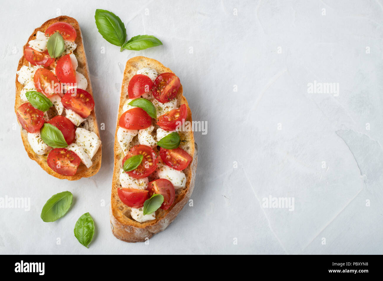Bruschetta with tomatoes, mozzarella cheese and basil on a light background. Traditional italian appetizer or snack, antipasto. Top view with copy spa - Stock Image