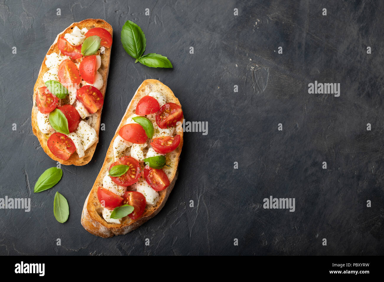 Bruschetta with tomatoes, mozzarella cheese and basil on a black background. Traditional italian appetizer or snack, antipasto. Top view with copy spa - Stock Image