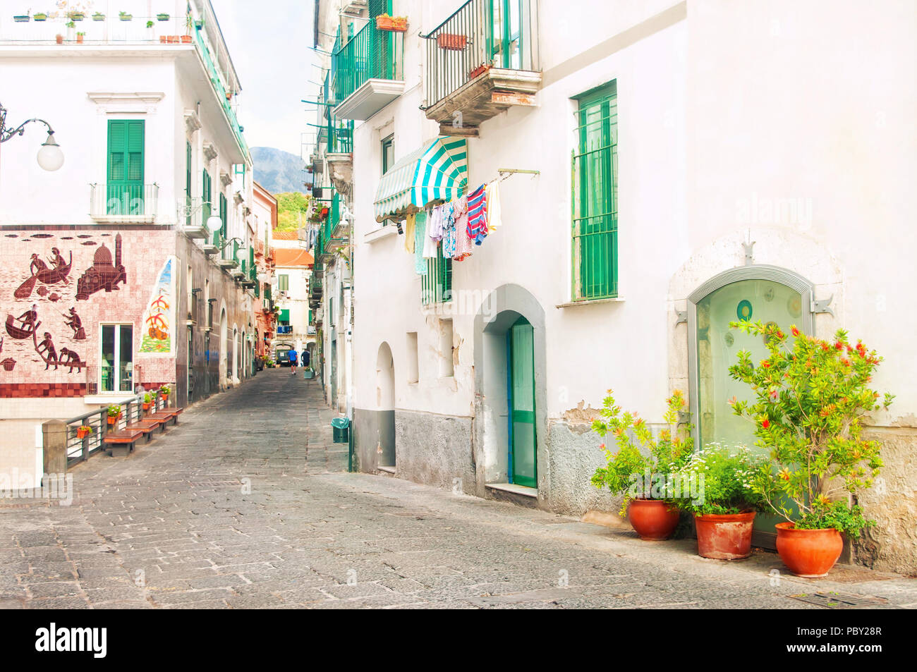 narrow street in small Italian town famous for its ceramic decoration on walls with flower pots and linen hanging on balcony Stock Photo