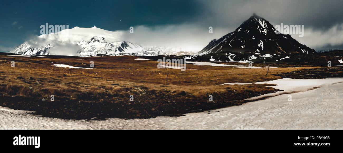 Panorama Image Night View snaefellsnesjokull Iceland with grass and blue sky stars with clouds and with view towards mountain. Southern side if the country. - Stock Image