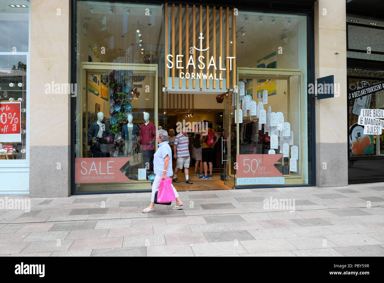 Shopper walking past the Seasalt Cornwall clothing store in Cardiff City Centre Wales UK    KATHY DEWITT - Stock Image