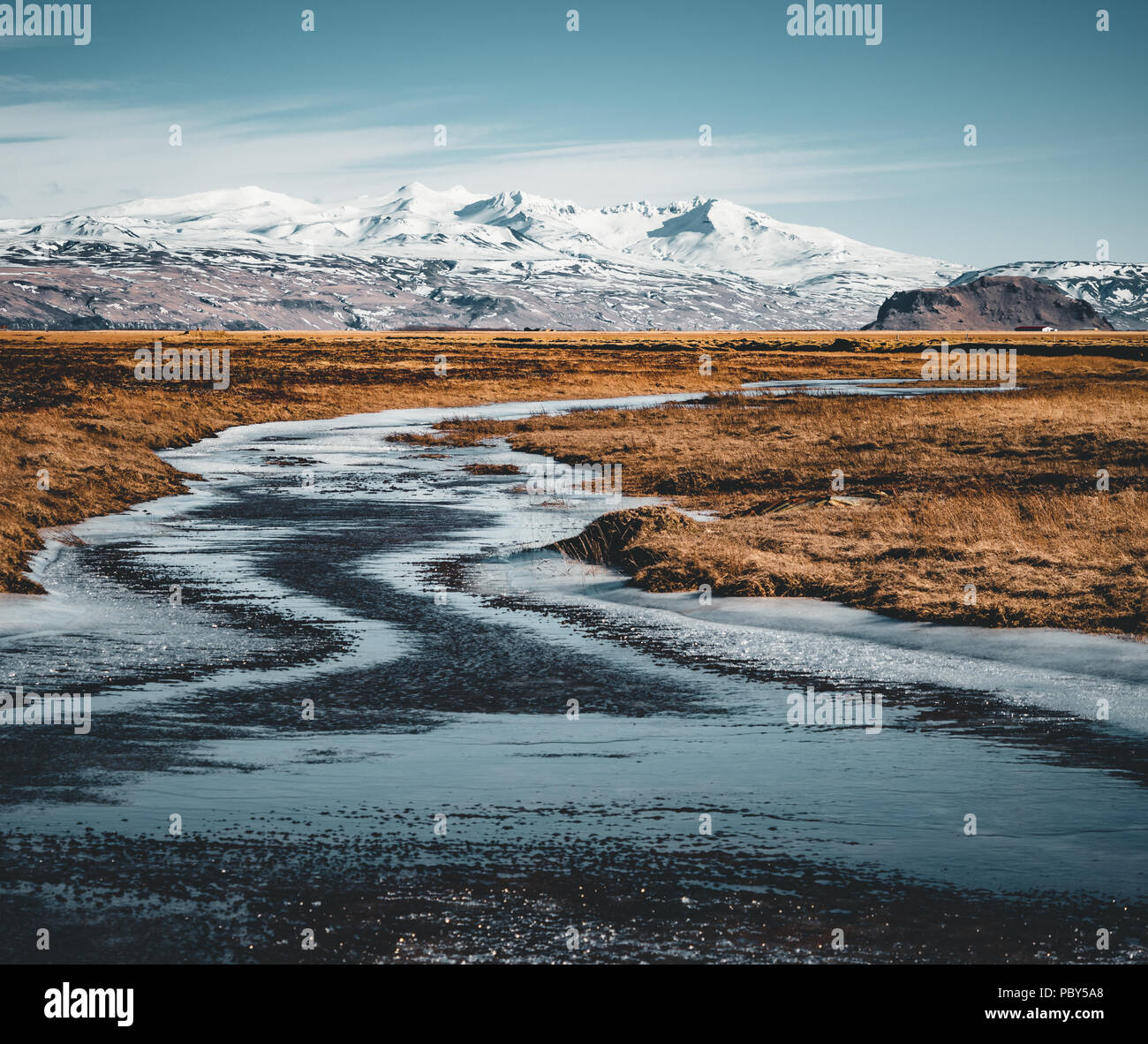 Iceland typical mountain winter scene with grass in foreground and massive mountain in background. - Stock Image