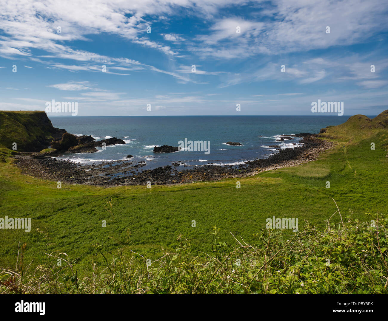 Small bay with black stones on the coast of Causeway with a green field in the foreground Stock Photo