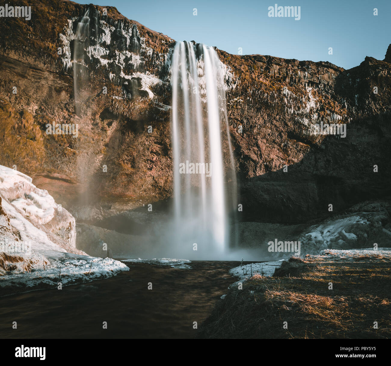 Wonderful landscape from Seljalandsfoss Waterfall in Iceland on a clear day with blue sky and snow. - Stock Image