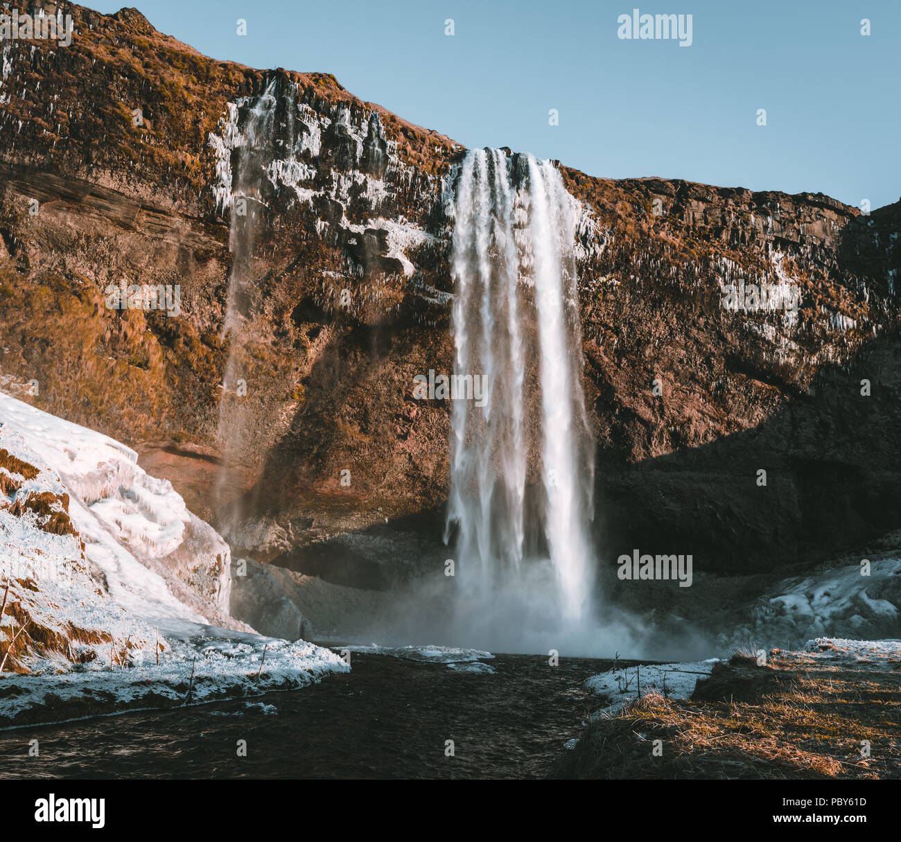 Wonderful landscape from Seljalandsfoss Waterfall in Iceland on a clear day with blue sky and snow. Stock Photo