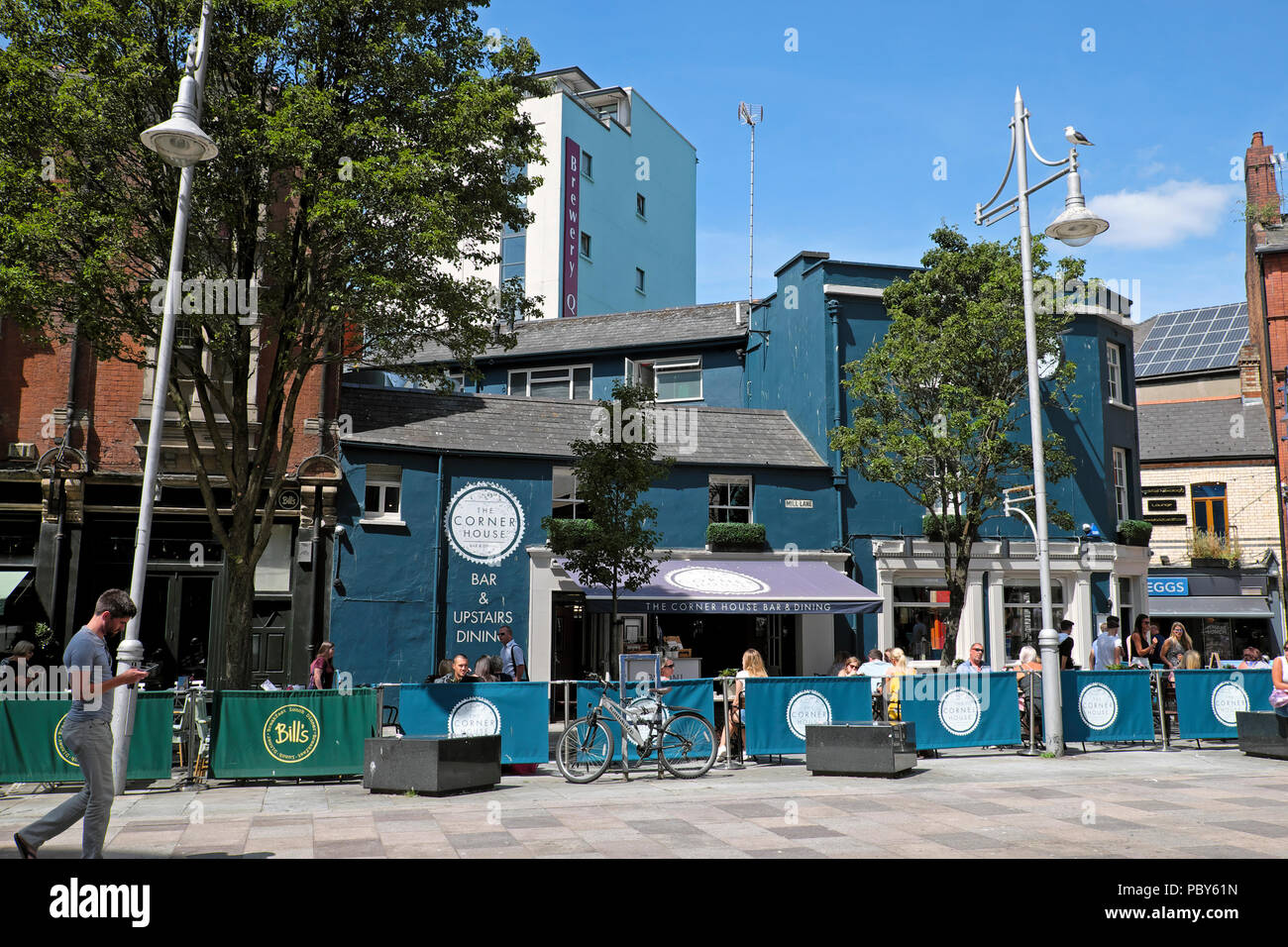 Exterior view of people eating at tables outside The Corner House bar and restaurant in Cardiff city centre Wales UK  KATHY DEWITT - Stock Image