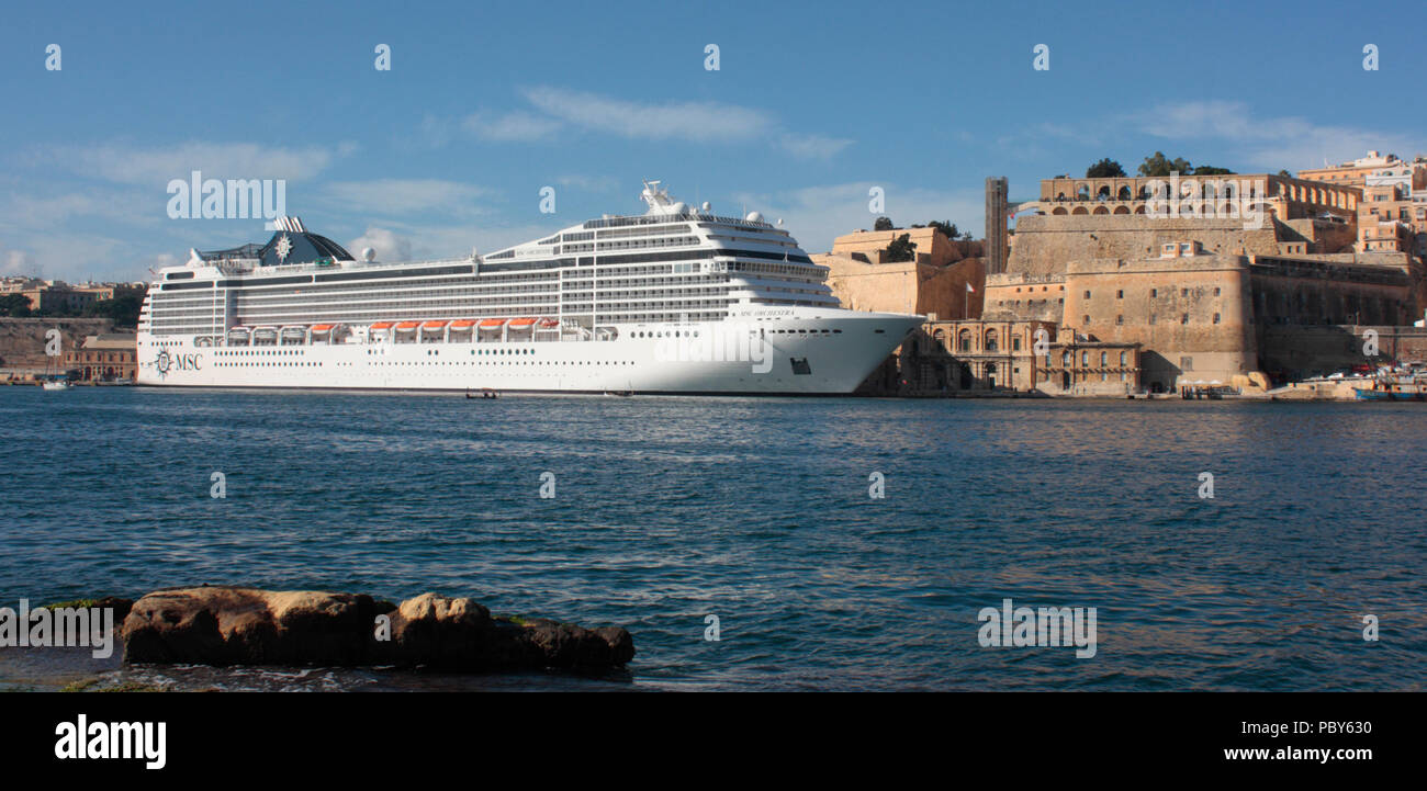 The cruise ship MSC Orchestra moored by the walls of Valletta in the Grand Harbour, Malta. Holiday travel in the Mediterranean Sea. - Stock Image