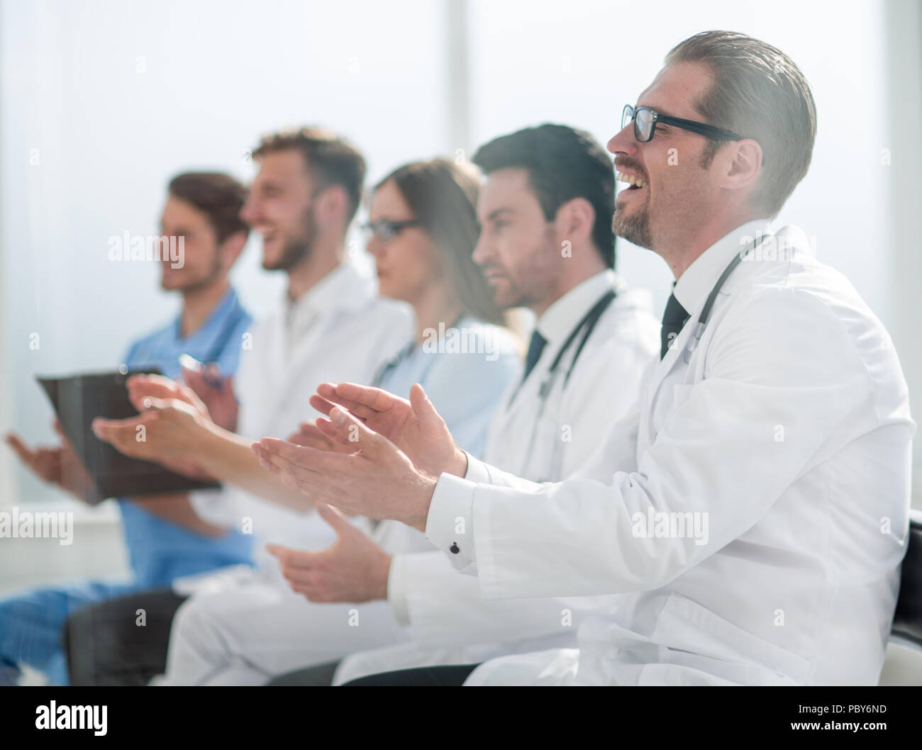Medical team applauding in meeting - Stock Image