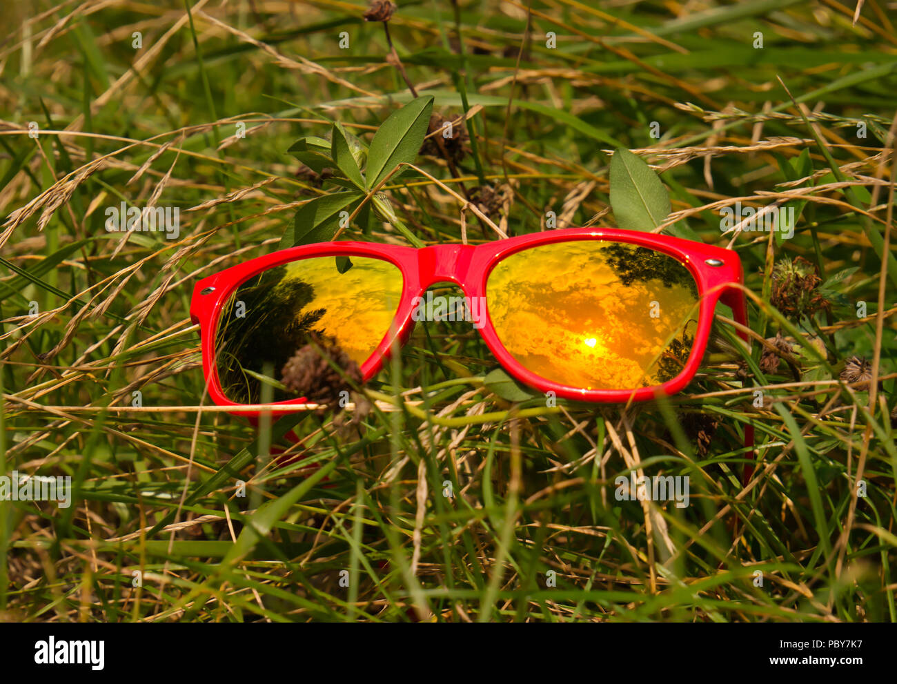 Clouds and sun reflection in glass of sunglasses with red plastic frame on a meadow in the grass - Stock Image