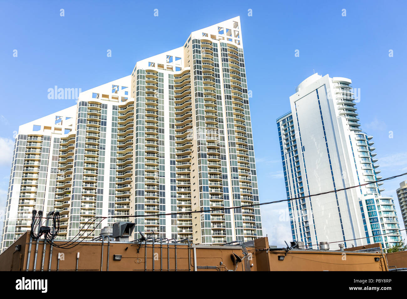 Sunny Isles Beach, USA - May 4, 2018: Apartment condo hotel Pinnacle building balconies during sunny day in Miami, Florida with skyscrapers urban back - Stock Image