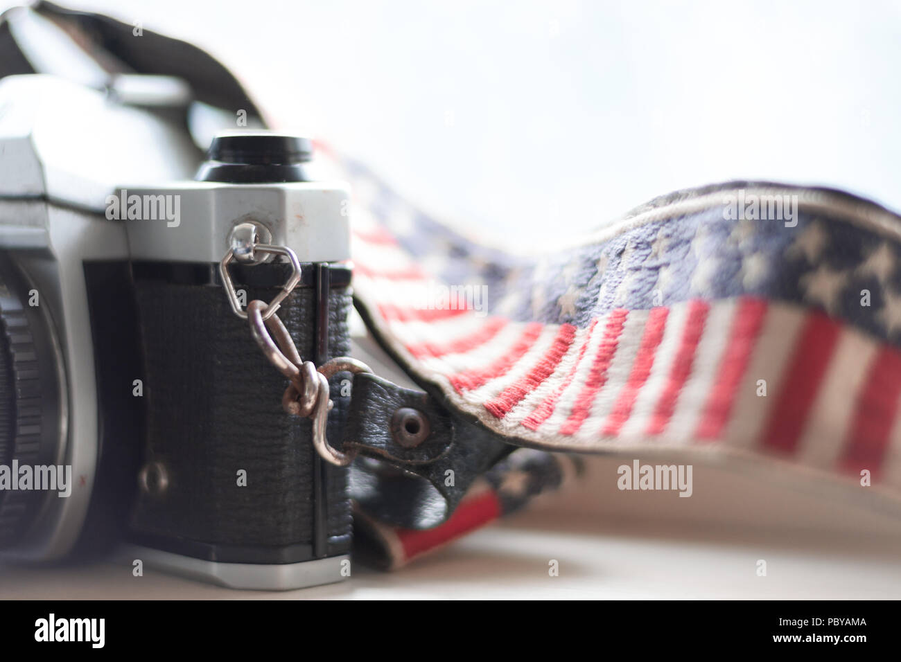Close up of a film SLR camera and American flag strap on a white background. - Stock Image