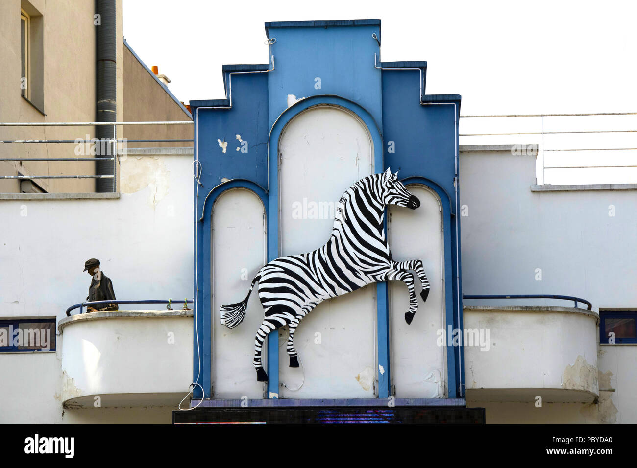Upper part of a former cinema in Belleville, Paris, with jumping zebra and a shop mannequin that has seen better days...now the home of cabaret/circus - Stock Image