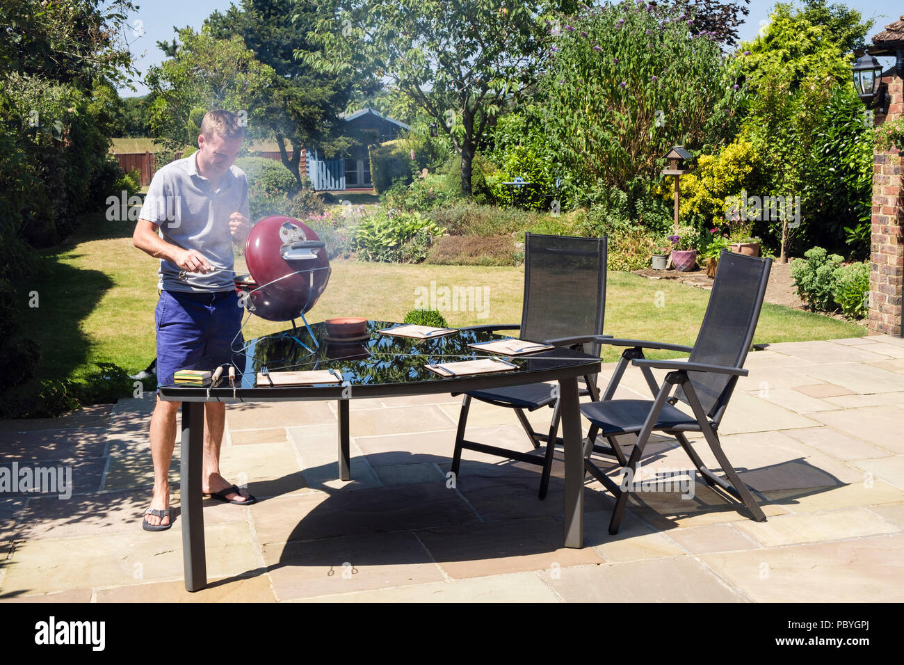 Young Millennial man cooks on a BBQ on a domestic back garden table on a patio in hot summer of 2018. England, UK, Britain Stock Photo