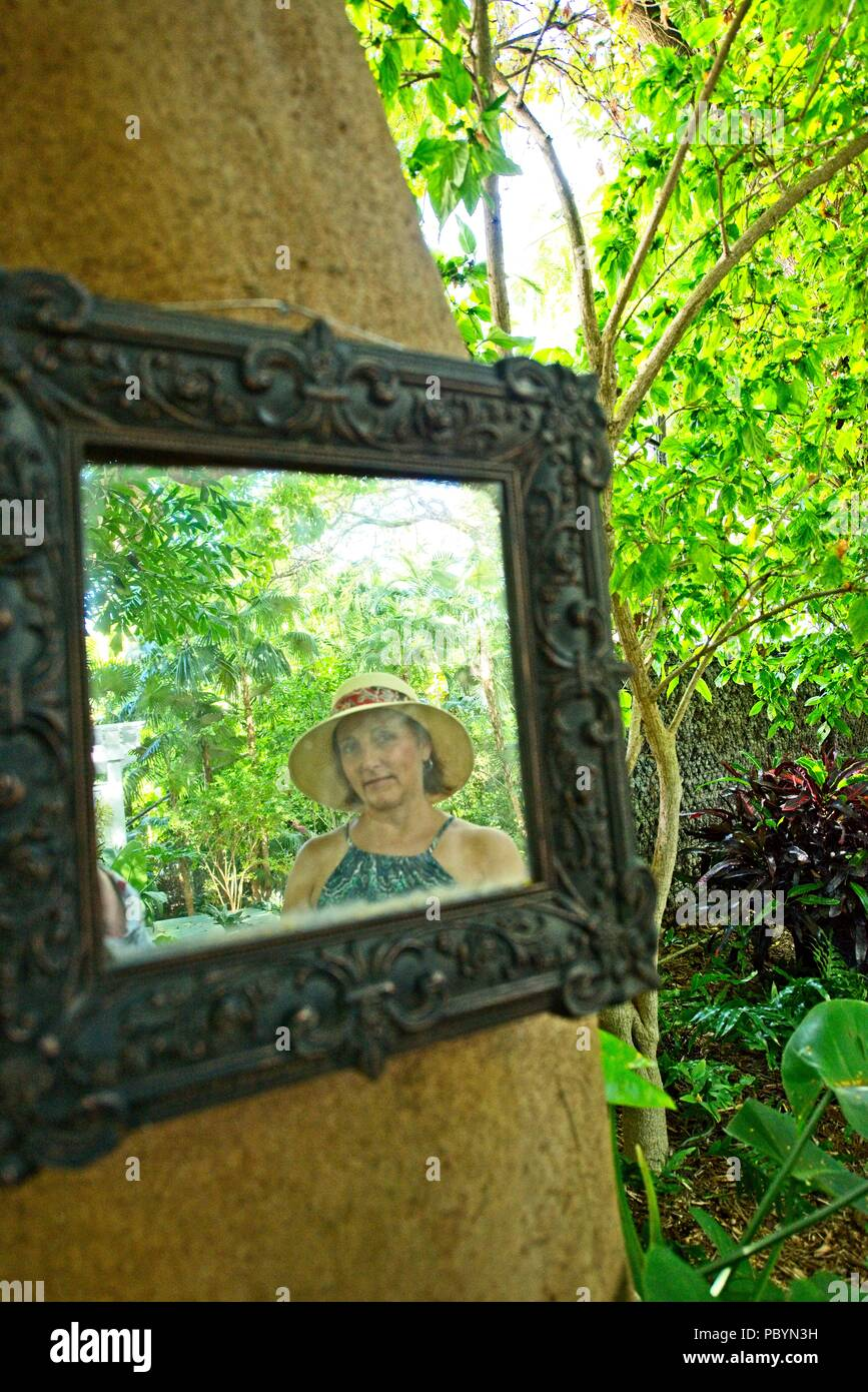 A reflection of a woman wearing a sun hat and sundress in a mirror hanging on a tree in an outdoor tropical environment - Stock Image