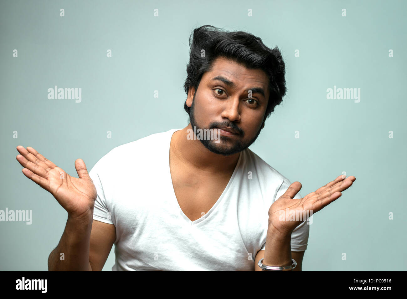 close up portrait of handsome Indian man showing indifference to the problem, situation. puzzled face Stock Photo