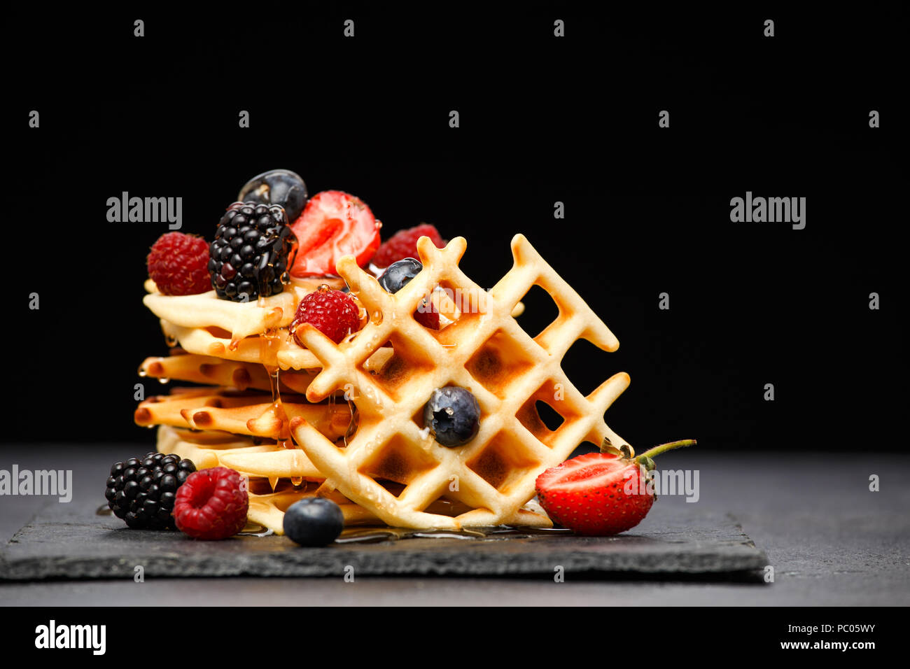 Photo of viennese wafers with berries pouring honey on black background - Stock Image