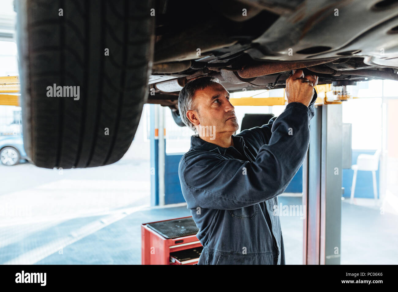 Car mechanic working on a lifted automobile at service station. Experienced repair man working in his garage. - Stock Image