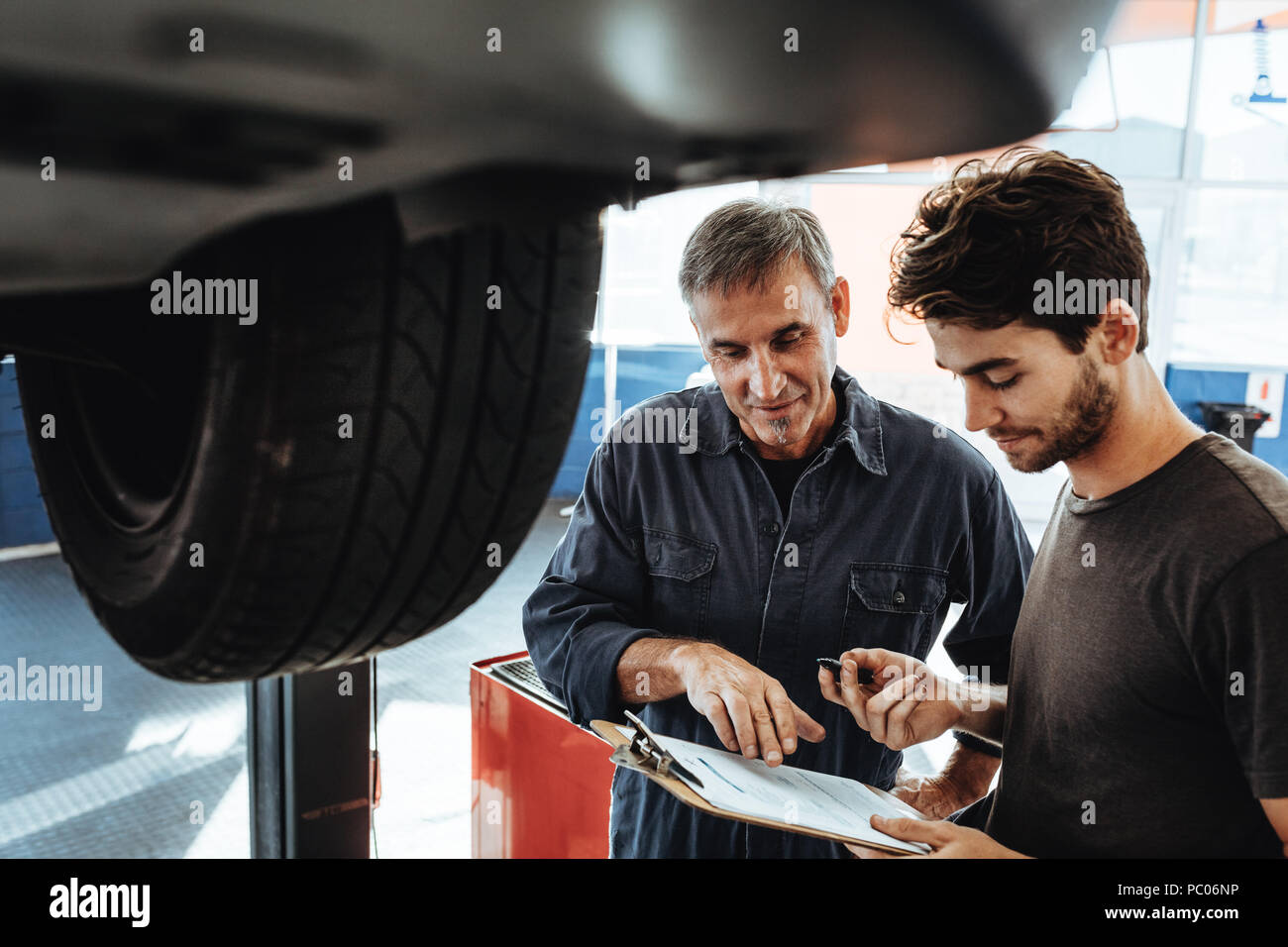 Mechanics in uniform making notes while standing by a car in auto service station. Two people working in auto garage and making a list of problems in  - Stock Image